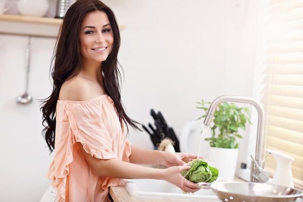 Jonge vrouw die sla in moderne keuken wast
