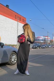 Jonge vrouw die sleutel van haar auto in de zak zoekt