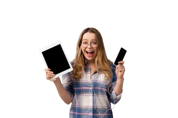 Jonge vrouw die smartphone, apparaten, gadgets gebruikt die op witte studiomuur worden geïsoleerd