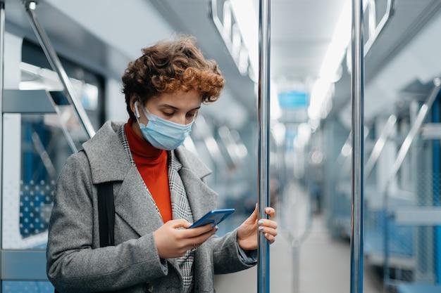 Jonge vrouw die smartphone gebruikt tijdens metrorit