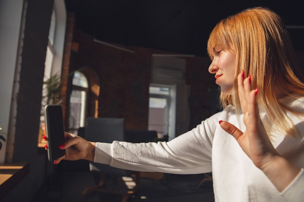 Jonge vrouw die smartphone gebruikt voor videobellen