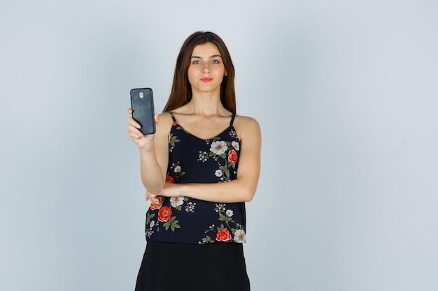 Jonge vrouw die smartphone in blouse, rok houdt en er tevreden uitziet. vooraanzicht.
