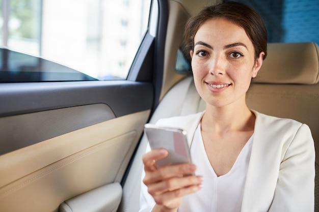 Jonge vrouw die smartphone in taxi gebruiken