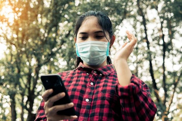 Jonge vrouw die smartphone, sociaal distantiërend concept gebruiken.