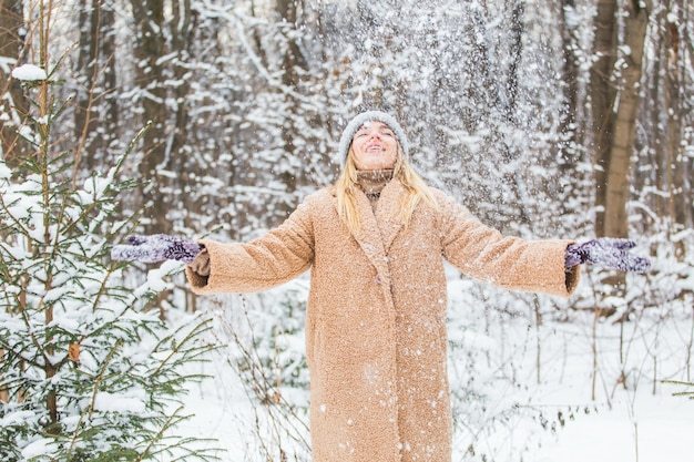 Jonge vrouw die sneeuw in de lucht gooit op een zonnige winterdag, ze is blij en leuk.