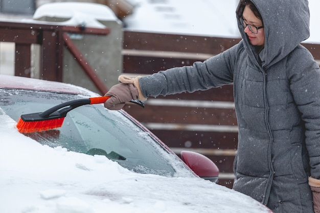 Jonge vrouw die sneeuw van auto borstelt na zware sneeuwval