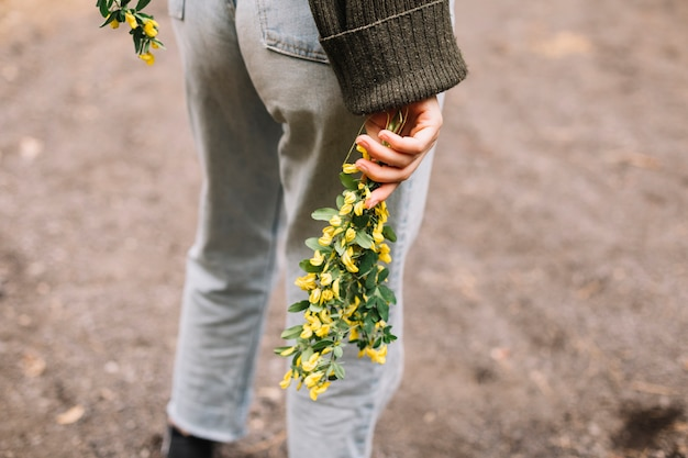 Jonge vrouw die sommige wildflowers houdt