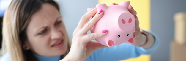 Jonge vrouw die spaarvarken met geld schudt