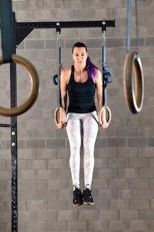 Jonge vrouw die spier omhoog oefeningen op ringen doet