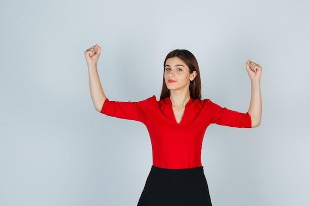 Jonge vrouw die spieren in rode blouse, zwarte rok toont en zelfverzekerd kijkt