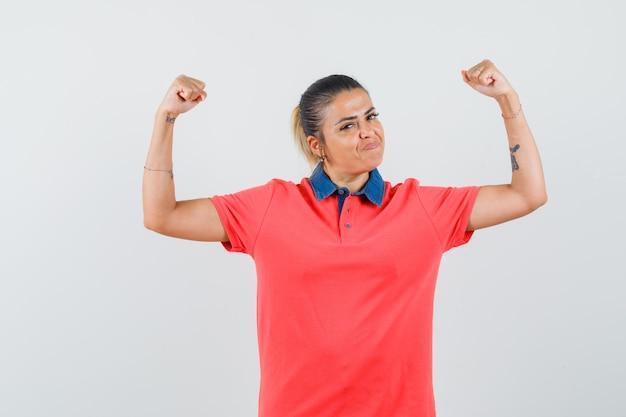 Jonge vrouw die spieren in rood t-shirt toont en zelfverzekerd, vooraanzicht kijkt.