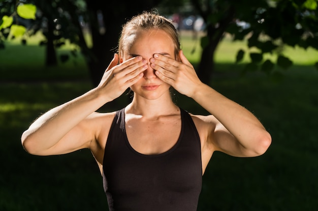 Jonge vrouw die sportkleding in het park draagt