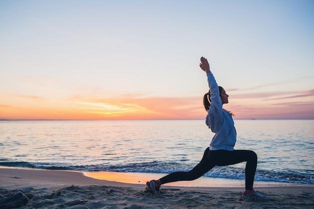 Jonge vrouw die sportoefeningen doet op zonsopgangstrand in ochtend