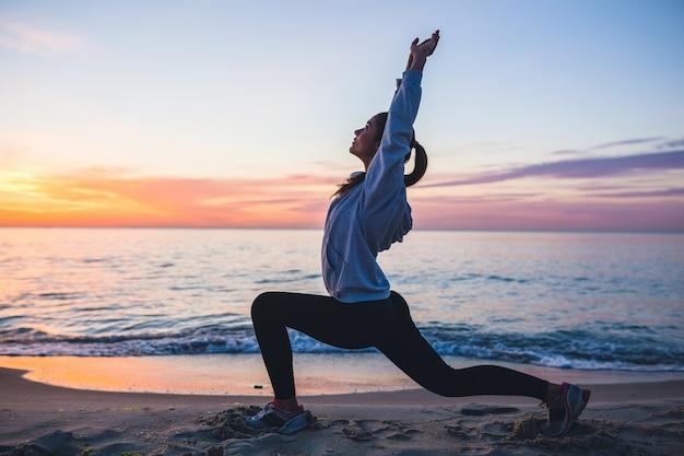 Jonge vrouw die sportoefeningen op zonsopgangstrand in ochtend doet