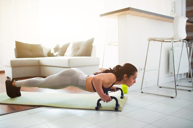 Jonge vrouw die sporttraining doet in de kamer tijdens quarantaine. fitnessmodel staat in plankpositie met behulp van push-up stand-handstang. ook omhoog duwen op de mat.