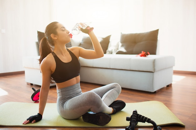 Jonge vrouw die sporttraining in ruimte doen tijdens quarantaine. rust na het sporten. het meisje zit op mat en drinkt water uit plastic fles. pauzeer na wokrout.