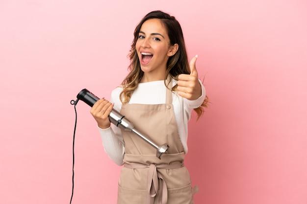 Jonge vrouw die staafmixer gebruikt over geïsoleerde roze achtergrond met duimen omhoog omdat er iets goeds is gebeurd