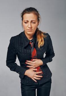 Jonge vrouw die staat en haar buik vasthoudt alsof ze ziek of ongemakkelijk is