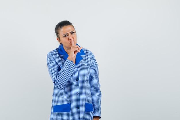Jonge vrouw die stilte gebaar toont, wijsvinger op lippen zet in het blauwe overhemd van de ginghampyjama en ernstig, vooraanzicht kijkt.