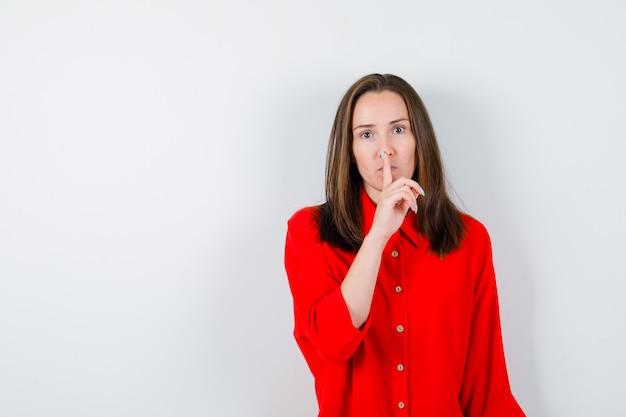Jonge vrouw die stiltegebaar in rode blouse toont en ernstig, vooraanzicht kijkt.
