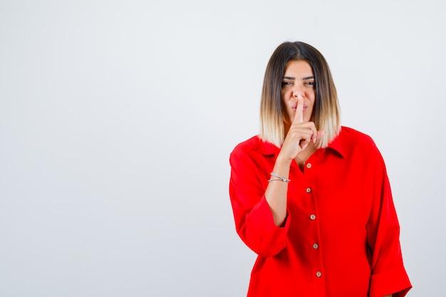 Jonge vrouw die stiltegebaar in rood oversized shirt toont en zelfverzekerd kijkt, vooraanzicht.
