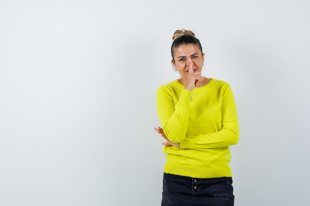 Jonge vrouw die stiltegebaar in trui, spijkerrok toont en er gelukkig uitziet