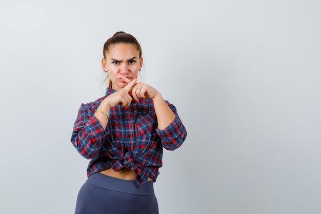 Jonge vrouw die stiltegebaar toont met gekruiste vingers in geruit hemd, broek en er serieus uitziet. vooraanzicht.
