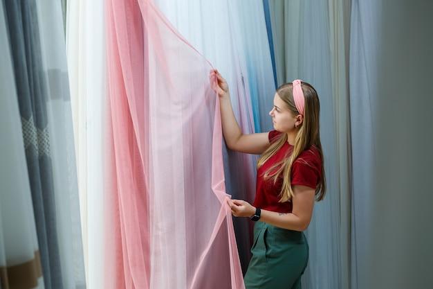 Jonge vrouw die stof kiest voor nieuwe gordijnen in een winkel. monsters van het gordijn hangen aan hangers aan een rail in de winkel. voorbeelden van texturen van stof, tule en meubelbekleding.