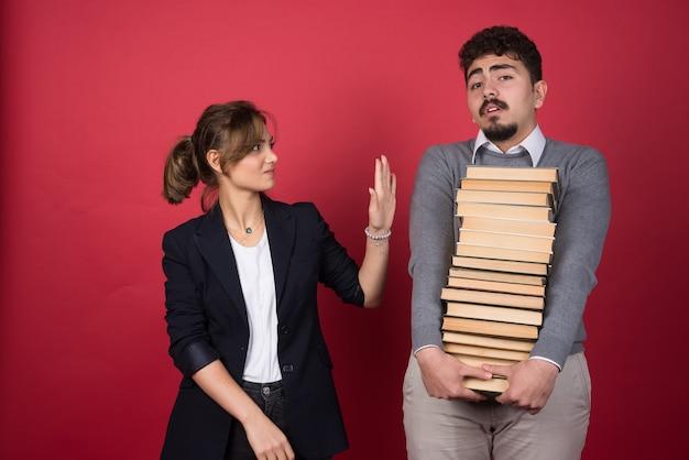 Jonge vrouw die stop vertelt aan man die bos boeken draagt