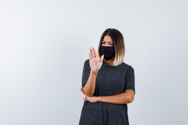Jonge vrouw die stopbord toont, hand onder elleboog in zwarte kleding, zwart masker houdt en boos kijkt. vooraanzicht.