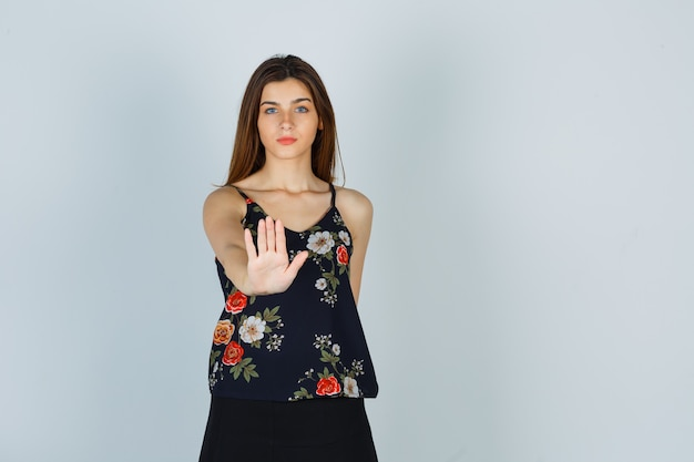 Jonge vrouw die stopgebaar in bloementop toont en zelfverzekerd kijkt