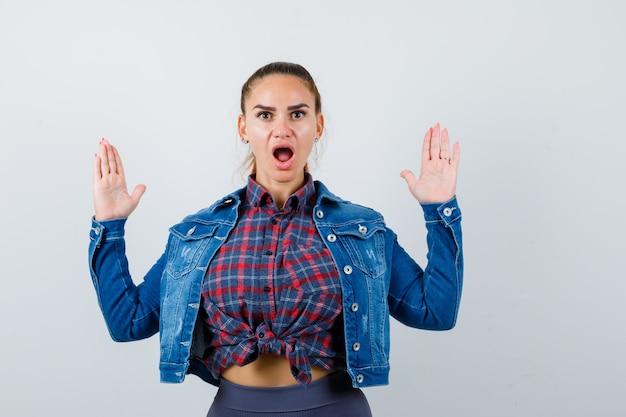 Jonge vrouw die stopgebaar in geruit overhemd, jeansjasje toont en geschokt kijkt, vooraanzicht.