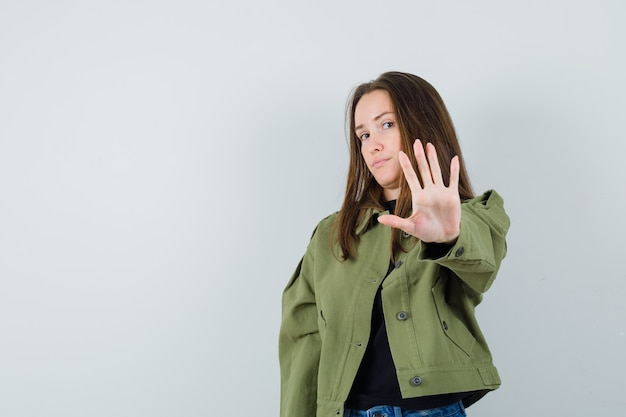 Jonge vrouw die stopgebaar in groene jas toont en aandachtig kijkt. vooraanzicht.