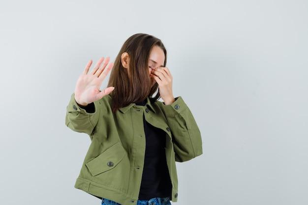 Jonge vrouw die stopgebaar in groene jas toont en verveeld kijkt. vooraanzicht.