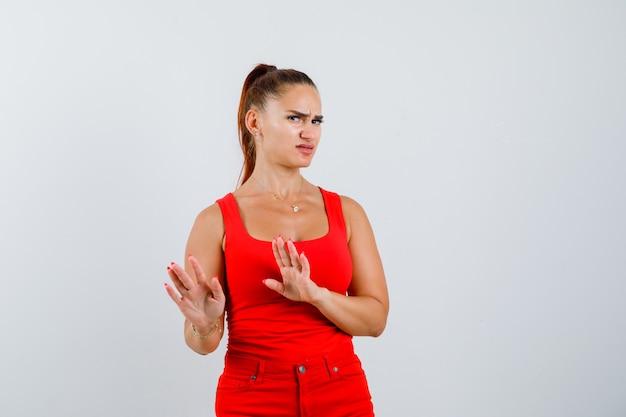Jonge vrouw die stopgebaar in rood mouwloos onderhemd, broek toont en ontevreden, vooraanzicht kijkt.