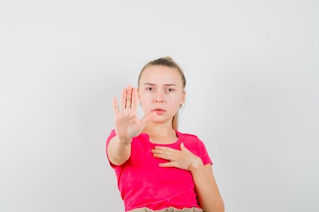 Jonge vrouw die stopgebaar in t-shirt toont en geïrriteerd kijkt