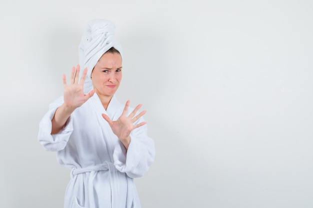 Jonge vrouw die stopgebaar in witte badjas, handdoek toont en walgt op zoek. vooraanzicht.