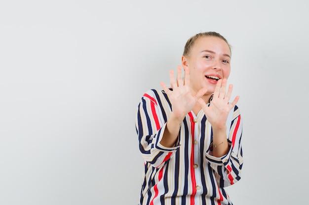 Jonge vrouw die stopgebaren met beide handen toont en in gestreepte blouse lacht en gelukkig kijkt