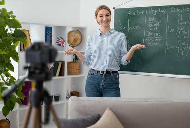 Jonge vrouw die studenten in engelse klas online onderwijst