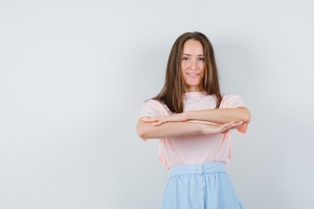 Jonge vrouw die stuk van flits-mob-dans in t-shirt, rok uitvoert en vrolijk kijkt. vooraanzicht.