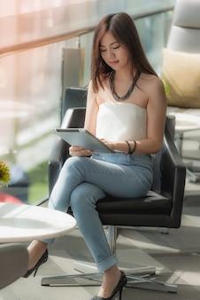 Jonge vrouw die tablet in de bouw van het glazenbureau gebruiken.