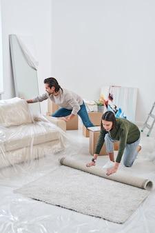 Jonge vrouw die tapijt op de vloer van de woonkamer uitrolt terwijl haar echtgenoot dichtbij een nieuwe bank verwijdert