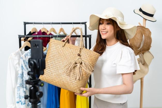Jonge vrouw die tas en hoed online verkoopt via live streaming van smartphone, zakelijke online e-commerce thuis