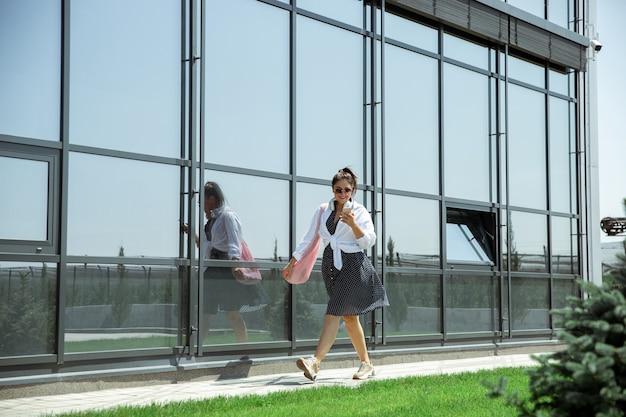 Jonge vrouw die tegen de glazen muur loopt op de luchthaven, reiziger met kleine bagage, de levensstijl van influencers of bloggers. kaukasisch vrouwelijk model met gadgets voordat ze aan haar vakantie begint, registratie.