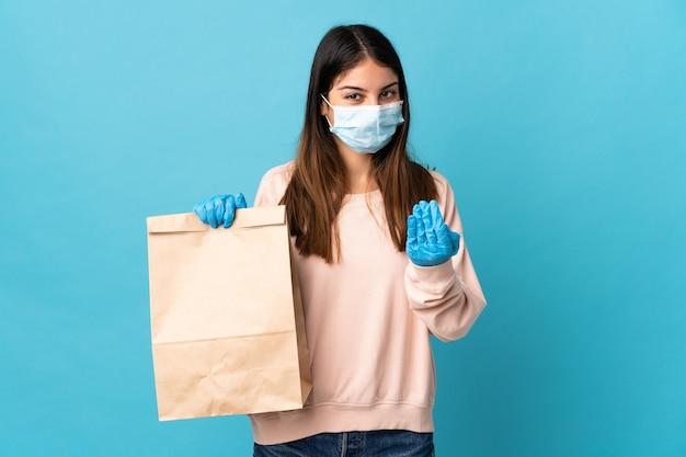 Jonge vrouw die tegen het coronavirus beschermt met een masker en een boodschappentas houdt die op blauw wordt geïsoleerd en uitnodigt om met de hand te komen. blij dat je gekomen bent