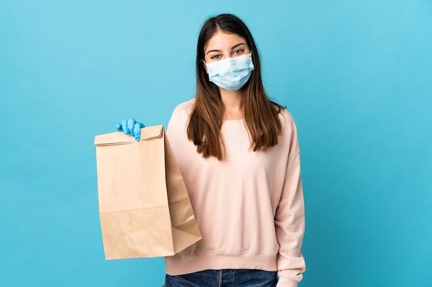 Jonge vrouw die tegen het coronavirus beschermt met een masker en een boodschappentas houdt die op blauwe muur wordt geïsoleerd die veel glimlacht