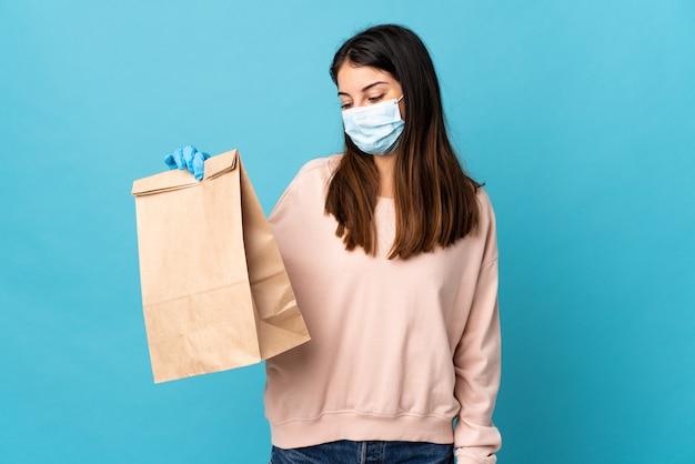 Jonge vrouw die tegen het coronavirus met een masker beschermt en een kruidenierswinkeltas houdt die op blauw met gelukkige uitdrukking wordt geïsoleerd