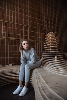 Jonge vrouw die tegen kunstbeeldhouwwerk leunen