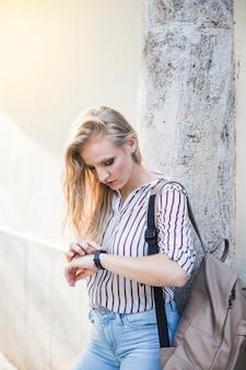 Jonge vrouw die tegen muur leunt die tijd op polshorloge bekijkt