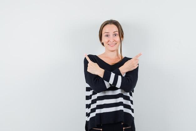 Jonge vrouw die tegengestelde richtingen met wijsvingers in gestreepte breigoed en zwarte broek toont en gelukkig kijkt